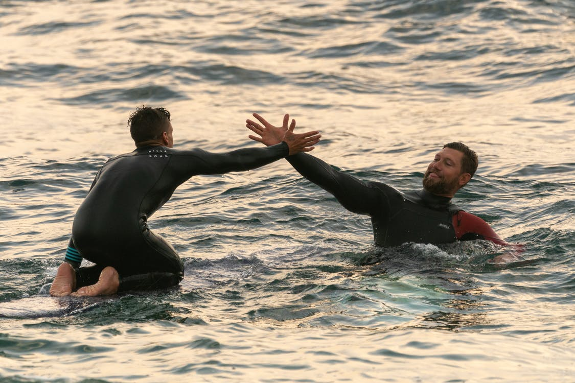 Surfers high-five